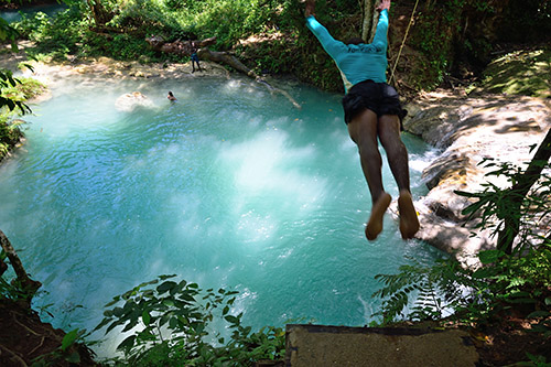 Devroe, our guide at the Blue Hole, leaps from a ledge into the turquoise water of the Blue Hole in Ocho Rios at the Jamaica port for Royal Caribbean's Navigator of the Seas on our Caribbean Cruise vacation